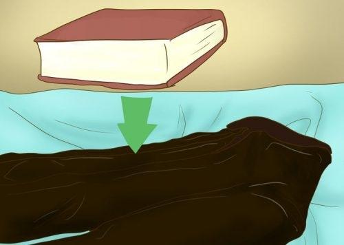 Положите толстую книгу на смятое место на одежде