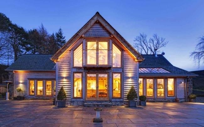 Фасад каркасного дома отделан натуральным деревом